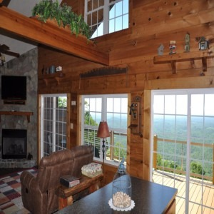 Cabin Living Room With Wall of Windows Looking Out on Deck and Long Range Views